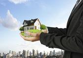 Huis in menselijke handen — Stockfoto
