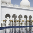 Stock Photo: Abu-Dhabi Grand Moss archway and outdoor pool water reflections