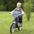 Boy riding a bicycle on grass field — Stock Photo