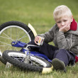 Upset little boy sits near to his bike — Stock Photo