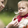 Kid and mother blowing dandelion — Stock Photo