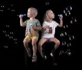 Little boy and girl flow bubbles — Stock Photo