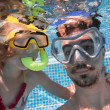 Stock Photo: Father and his daughter under water in pool