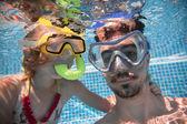 Pai e filha dele debaixo d'água na piscina — Fotografia Stock