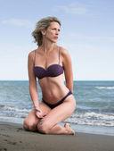 Bella donna bionda si inginocchia presso la spiaggia di sabbia — Foto Stock