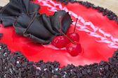Chocolate cake with a red cherry — Stock Photo