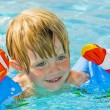 Stock Photo: Little girl learning to swim with pool noodle