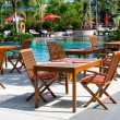 Stok fotoğraf: Table and chairs before pool