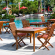Stock Photo: Table and chairs before pool
