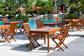 Table and chairs before pool — Stock Photo