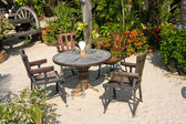 Table and chairs in a tropical garden — Stock Photo