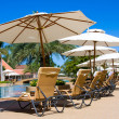 Lounge chairs by poolside - Stock Photo