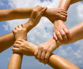 Many hands connecting to a chain with sky — Stock Photo