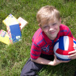 Boy on the grass holding a ball — Stock Photo