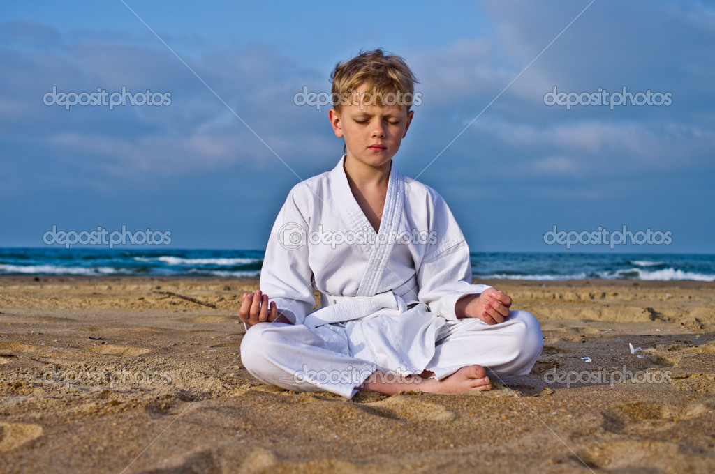 A boy in a kimono meditates on the beach. Background of sea and sky — Stock Photo #10943751