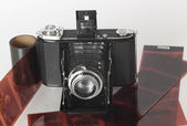 A vintage folding camera with some film — Stock Photo