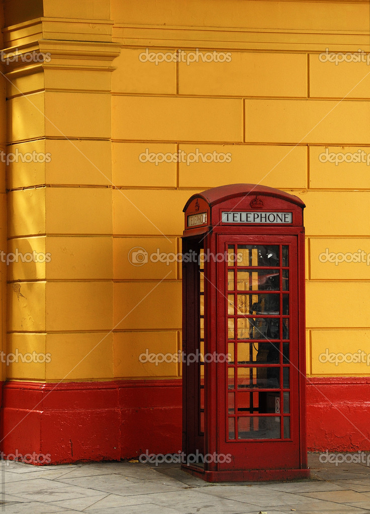 It is a red telephone box in London. A orange colored wall at the background — Stock Photo #11010085