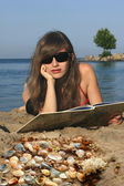 Girl with a book on the sea — Stock Photo