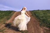 Bride dancing in a field — Stock Photo