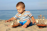 A little boy on the beach with a ship — Stock Photo