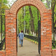 The red brick gate and a going out boy — Stock Photo