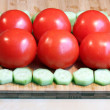 Fresh cucumbers and tomatoes on a wood chopping board — Stockfoto