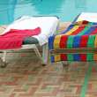 Relax chairs near pool with towels — Stock Photo #11529680