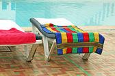 放松与毛巾在游泳池附近的椅子 — 图库照片
