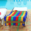 Relax chairs near pool with towels — Stock Photo #11829523