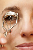 Portrait of young woman using an eyelash curler — Stock Photo
