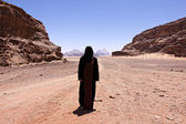 Nomadic woman with burka in the desert — Stock Photo