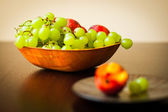 Fresh and tasty fruits in bowl on table — Stock Photo