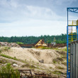 Stockfoto: Unusable equipment and new building at gravel pit