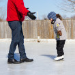 Father teaching daughter how to ice skate — Stok fotoğraf
