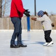 Father teaching daughter how to ice skate — Stock Photo