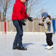 Father teaching daughter how to ice skate - Stock Photo