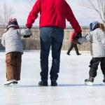 Family having fun at the skating rink — Stock Photo