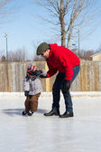 Father teaching son how to ice skate — Stock Photo