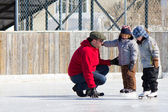 Family having fun at the skating rink — Stock Photo