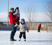 Happy family at the skating rink — Stock Photo