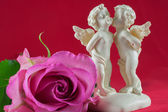 Angels kissing and pink rose — Stock Photo