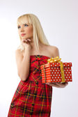 Pretty young blonde girl holding christmas gift in red dress — Stock Photo