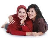 Mulher muçulmana com a filha deitada no isolado sobre backround branco — Fotografia Stock