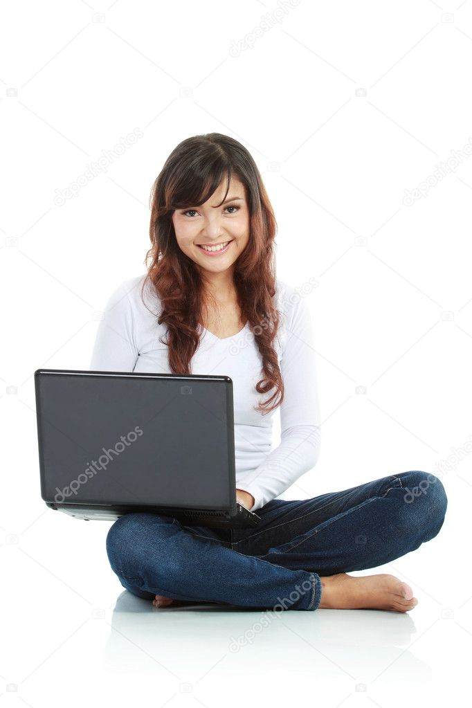 Young female sitting cross-legged on floor with laptop isolated white background  Stock Photo #10755665