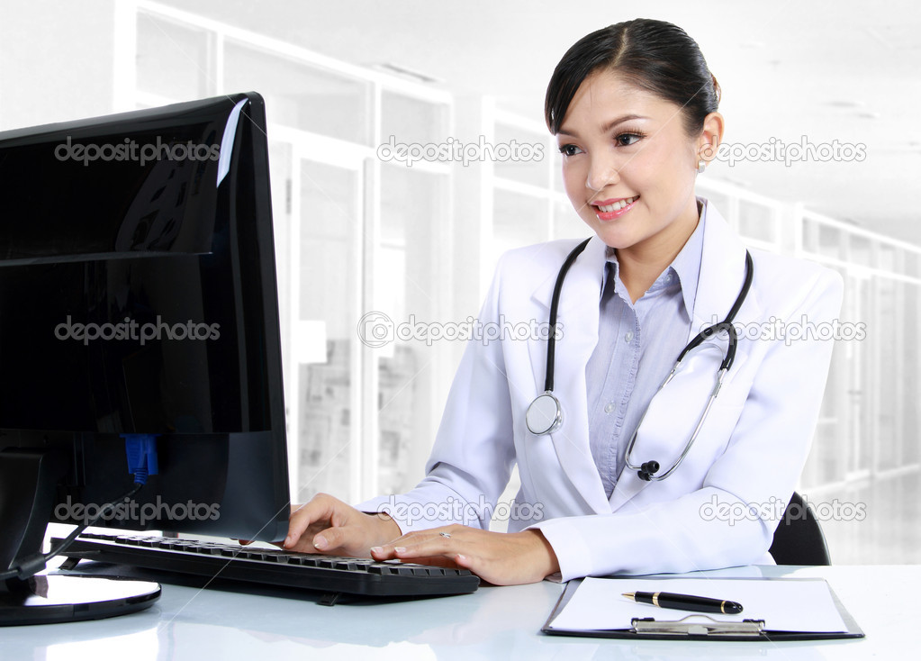 Front view of smiling woman doctor working on computer  Stock Photo #10755829