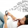 Woman texting on phone lying on bed — Stock Photo