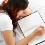 flicka skriver bok på sängen — Stockfoto