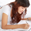 Girl writing book on the bed — Stock Photo #10956346