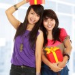 Stock Photo: Two young girls carrying present