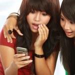 Surprised girls reading gossip — Stock Photo
